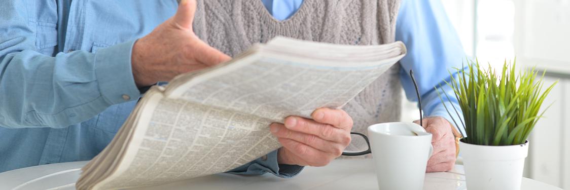 Åben avis foran en kaffekop og et par læsebriller