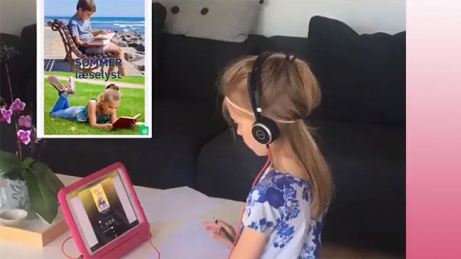 Smilla sidder og læser ved en iPad