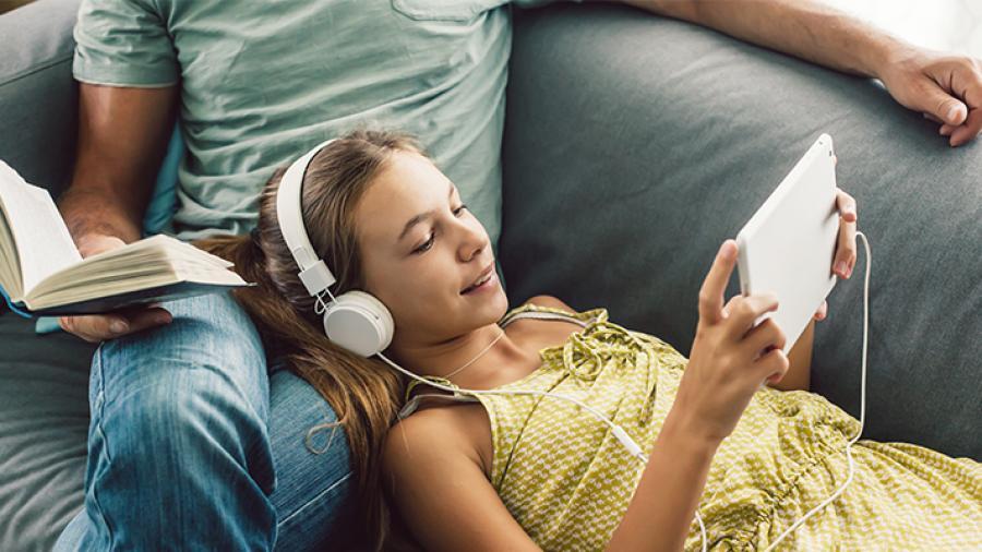 Pige ligger i sofa med headset og tablet