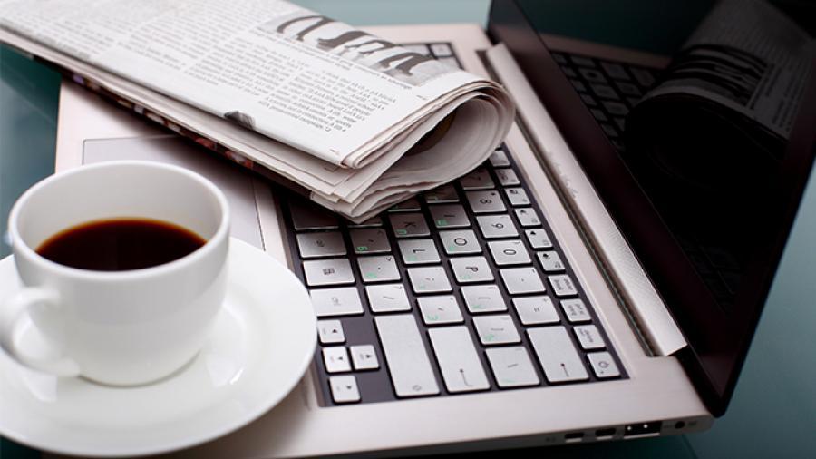 Sammenfoldet avis åben computer og en kop kaffe