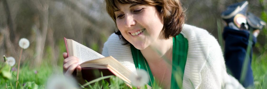 Pige der ligger i græsset og læser i en bog